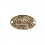 """Metallist, ovaalne, reljeefse mustriga """"Handmade"""" kahe küljelt auguga, suuruses 32x19x1,5mm"""